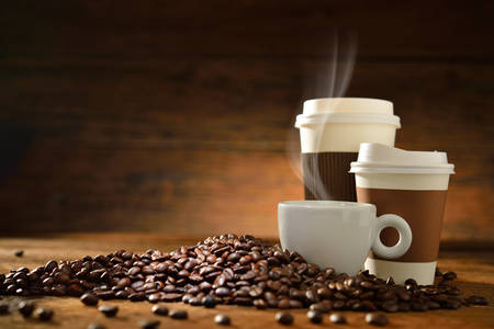 Foto für Cups of coffee with smoke and coffee beans on old wooden background - Lizenzfreies Bild