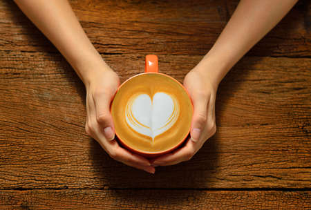 Foto für Woman holding cup of coffee latte, with heart shape - Lizenzfreies Bild