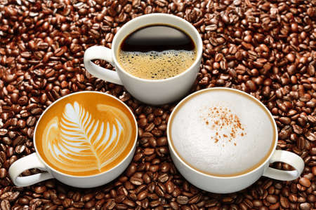 Foto für Variety of cups of coffee on coffee beans background - Lizenzfreies Bild