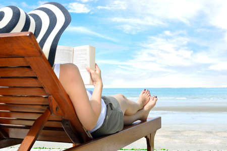 Photo pour Young woman reading a book at the beach - image libre de droit