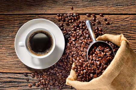 Foto de Cup of coffee and coffee beans on wooden table - Imagen libre de derechos