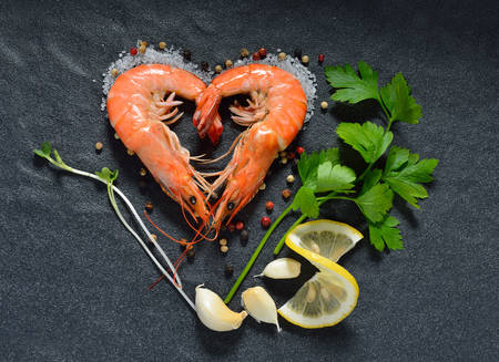 Foto de Cooked shrimps,prawns heart shape with seasonings on stone background - Imagen libre de derechos