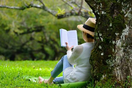 Photo pour Middle aged woman sitting under a tree reading a book in the park - image libre de droit