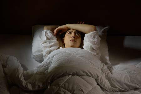 Foto de Woman with insomnia lying in bed with open eyes - Imagen libre de derechos