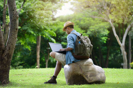 Foto per Young man traveling and working on laptop in the park - Immagine Royalty Free
