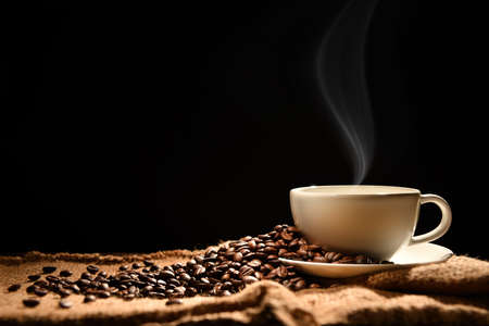 Foto de Cup of coffee with smoke and coffee beans on wooden background - Imagen libre de derechos