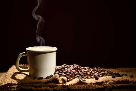 Foto de Cup of coffee with smoke and coffee beans on black background - Imagen libre de derechos