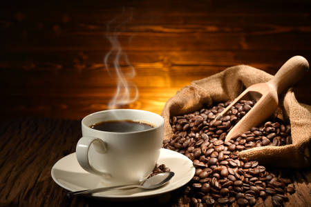 Foto de Cup of coffee with smoke and coffee beans on old wooden background - Imagen libre de derechos