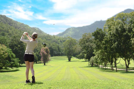 Photo for Young Asian woman playing golf on a beautiful natural golf course - Royalty Free Image