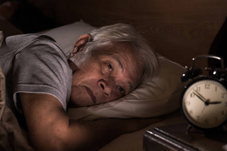 Photo pour Depressed senior man lying in bed cannot sleep from insomnia - image libre de droit