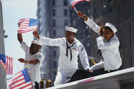 Foto de This is a Ticker Tape Parade showing the Desert Storm Victory Parade. It took place in the Canyon of Heroes where about 4.7 million people attended.  These are three sailors in white uniforms waving flags on a float. It demonstrates patriotism. - Imagen libre de derechos