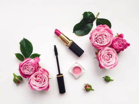 Photo for Decorative flat lay composition with mascara, lipstick and blush, decorated with flowers. Top view on white background, view from above - Royalty Free Image