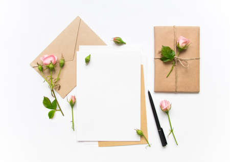 Foto de Letter, envelope and a present in eco paper on white background. Wedding invitation cards or love letter with pink roses. Valentine's day or other holiday concept, top view, flat lay, overhead view - Imagen libre de derechos