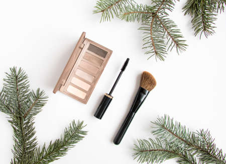 Winter cosmetics collage decorated with fir tree branches on white background. Eye shadows, mascara and brush, make up composition. Flat lay, top view