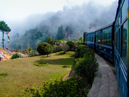 Train passing a beautiful garden and entering into fog  Surrounded by tree covered mountains