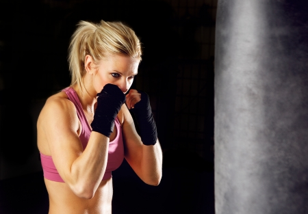 Young woman fitness boxing in front of punching bag  Isolated on black