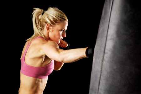 Young woman making a hard punch on a punching bag  Isolated on black