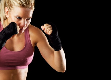 Portrait of a sexy fitness woman ready to fight  Isolated on black with copy space