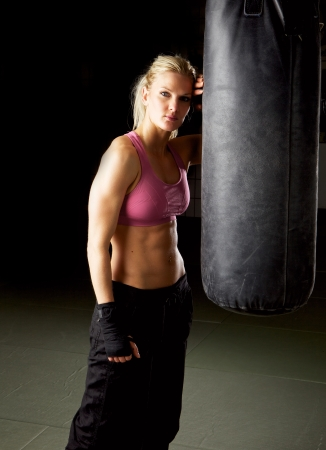 Portrait of a cool fit woman in gym standing against a punching bag