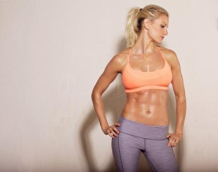 Foto de Confident athletic woman with sixpack abs posing - Imagen libre de derechos