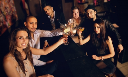Photo for Group of friends at the bar raising their glass for a toast - Royalty Free Image