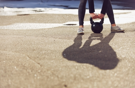 Photo for Shadow of a fitness crossfit woman lifting a kettlebell - Royalty Free Image