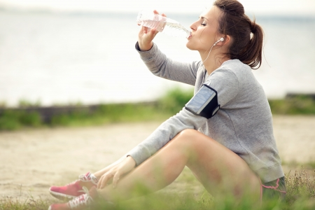 Photo pour Tired female jogger sitting on the grass and drinking bottled water - image libre de droit
