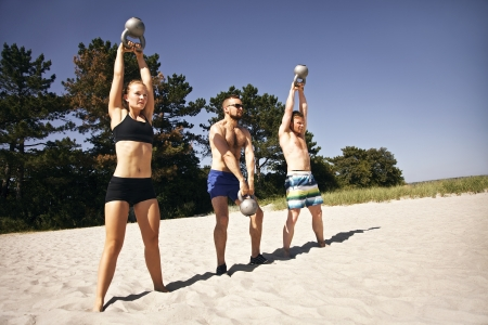 Photo for Group of athletes swinging a kettle bell over their head on beach - Royalty Free Image