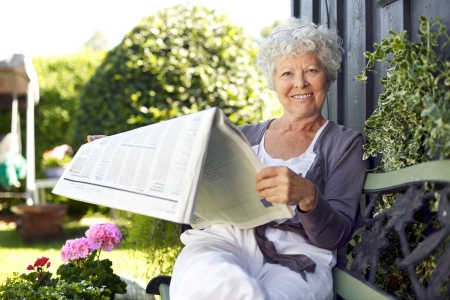 Foto per Relaxed senior woman sitting on a bench in backyard garden reading a newspaper looking at camera and smiling - Immagine Royalty Free