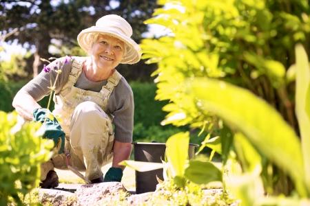 Foto de Happy elder woman with gardening tool working in her backyard garden - Imagen libre de derechos