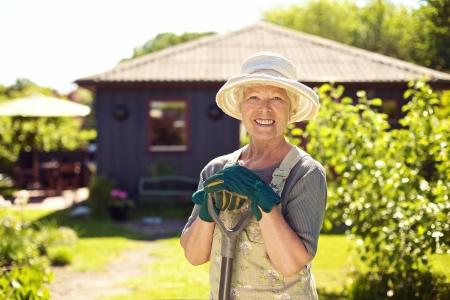 Foto de Portrait of cheerful senior woman with gardening tools outdoors. Older woman standing with shovel in her backyard garden - Imagen libre de derechos