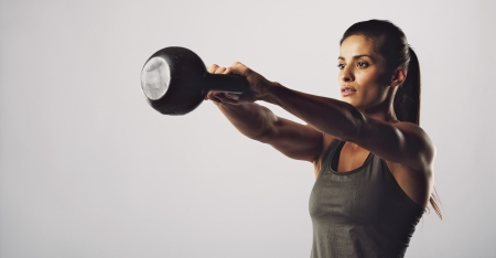 Photo for Young fitness female exercise with kettle bell. Mixed race woman doing crossfit workout on grey background. Kettlebell swing. - Royalty Free Image