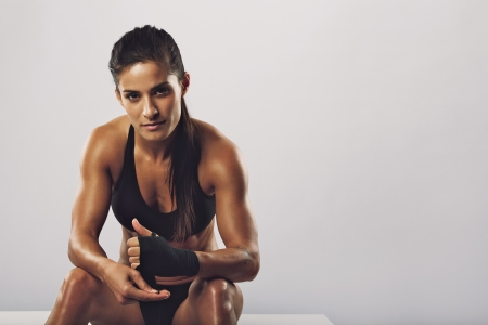 Photo pour Woman boxer wearing black strap on wrist for boxing practice, Fitness female sitting getting ready for boxing practice. Beautiful young woman with muscular body preparing for workout. - image libre de droit