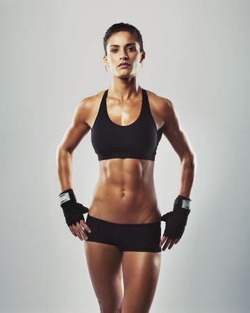 Photo for Portrait of sexy young woman with her hands on hips looking at camera. Fitness female with muscular body ready wearing hand gloves for workout on grey background - Royalty Free Image