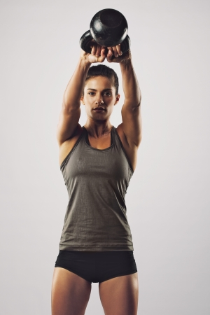 Photo for Young female doing swing exercise with a kettle bell. Fitness woman - Royalty Free Image