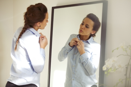 Foto de Attractive young woman in front of mirror buttoning up her shirt. Beautiful caucasian female getting dressed for office. - Imagen libre de derechos