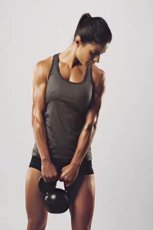 Photo for Fitness woman exercising crossfit holding kettle bell strength training biceps. Beautiful sweaty fitness instructor on grey background. Middle eastern female model with muscular fit and slim body. - Royalty Free Image