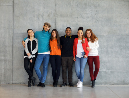 Photo for Group of stylish young university students on campus. Multiracial young people standing together against wall in college. - Royalty Free Image