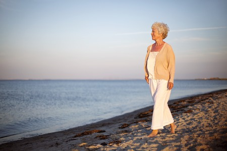 Photo for Portrait of a mature woman walking on the beach looking at the sea. Relaxed old lady strolling on the beach with lots of copyspace. - Royalty Free Image