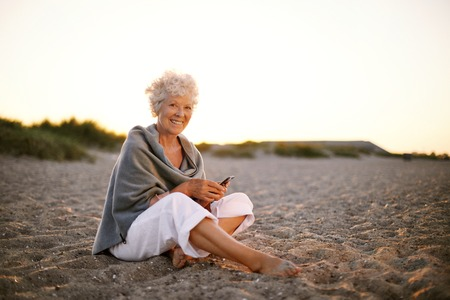 Foto de Happy retired woman sitting relaxed on beach holding a mobile phone in hand. Senior caucasian woman with cell phone on the beach outdoors - Imagen libre de derechos