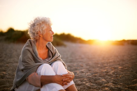 Photo pour Old woman sitting on the beach looking away at copyspace. Senior female sitting outdoors - image libre de droit
