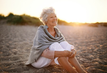 Foto de Happy retired woman wearing shawl sitting relaxed on sand at the beach. Senior caucasian woman sitting on the beach outdoors - Imagen libre de derechos