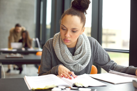 Foto de Female student reading a book for finding information. Young african american woman sitting at table doing assignments in university library. - Imagen libre de derechos