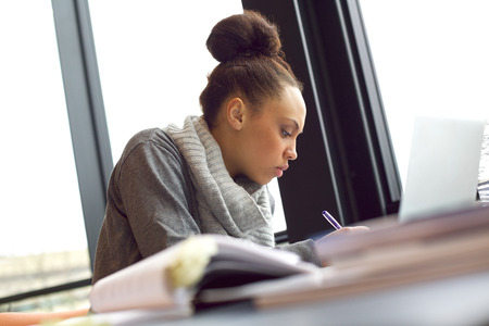 Photo for Young african american woman taking notes from books for her study. Sitting at table with books and laptop for finding information. - Royalty Free Image