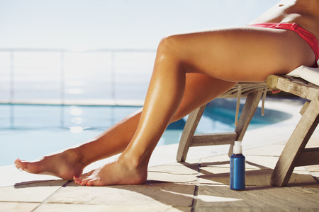 Young female relaxing on lounge chair with a suntan spray by the pool. Young lady sunbathing by the swimming pool.