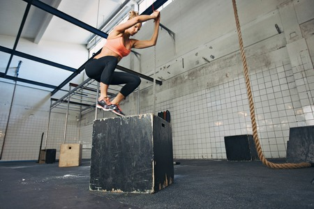 Foto de Fit young woman box jumping at a crossfit style gym. Female athlete is performing box jumps at gym. - Imagen libre de derechos