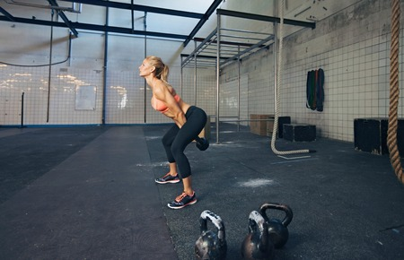 Photo for Young fitness female exercise with kettle bell. Caucasian woman doing crossfit workout at gym. - Royalty Free Image