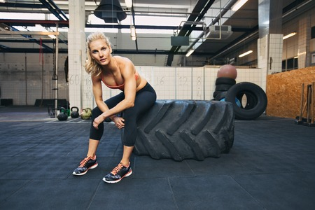 Photo for Fit young lady sitting on a big tire after her workout. Woman taking rest after exercise at gym. - Royalty Free Image