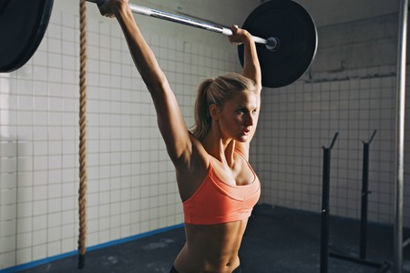 Foto de Strong woman lifting barbell as a part of crossfit exercise routine. Fit young woman lifting heavy weights at gym. - Imagen libre de derechos