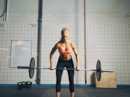 Photo pour Fit and attractive caucasian female holding a barbell in her hands. Crossfit woman lifting heavy weights in gym. - image libre de droit